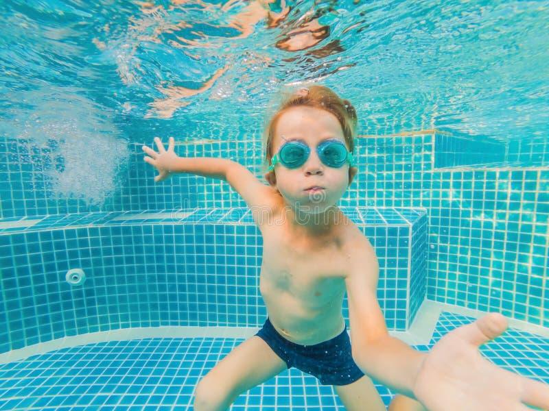 Divertimento novo subaquático do menino na piscina com óculos de proteção Divertimento das férias de verão fotos de stock