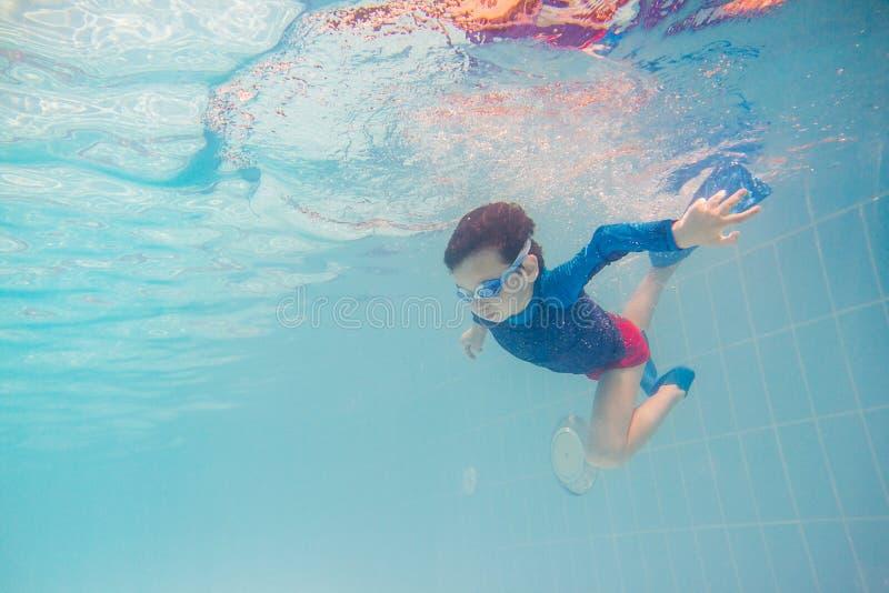 Divertimento novo subaquático do menino na piscina com óculos de proteção Divertimento das férias de verão foto de stock royalty free