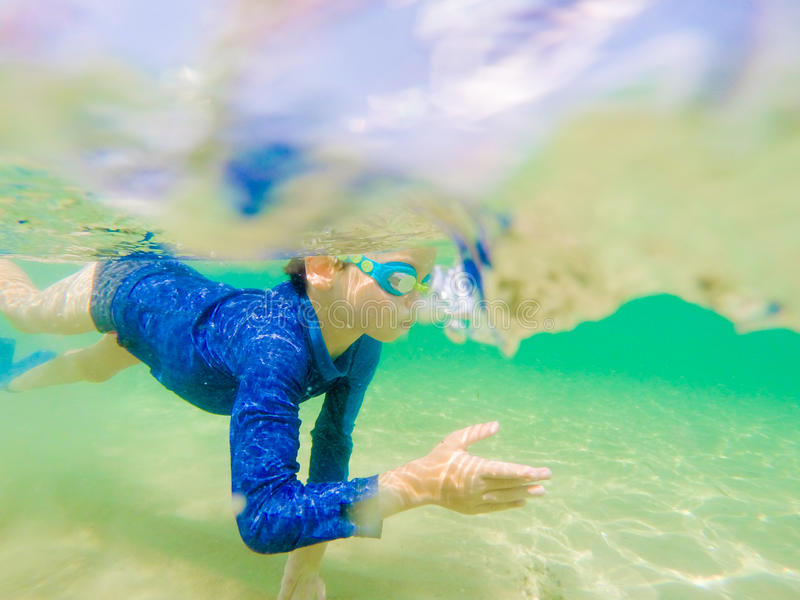 Divertimento novo subaquático do menino no mar com óculos de proteção Divertimento das férias de verão foto de stock