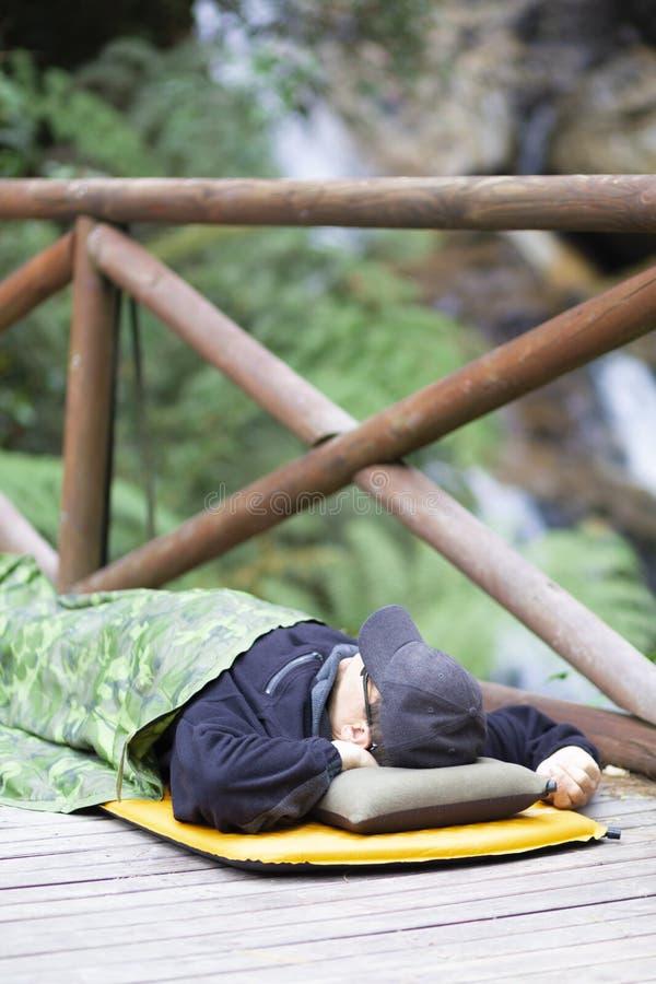 Divertimento que acampa, homem feliz que dorme na montanha fotos de stock royalty free