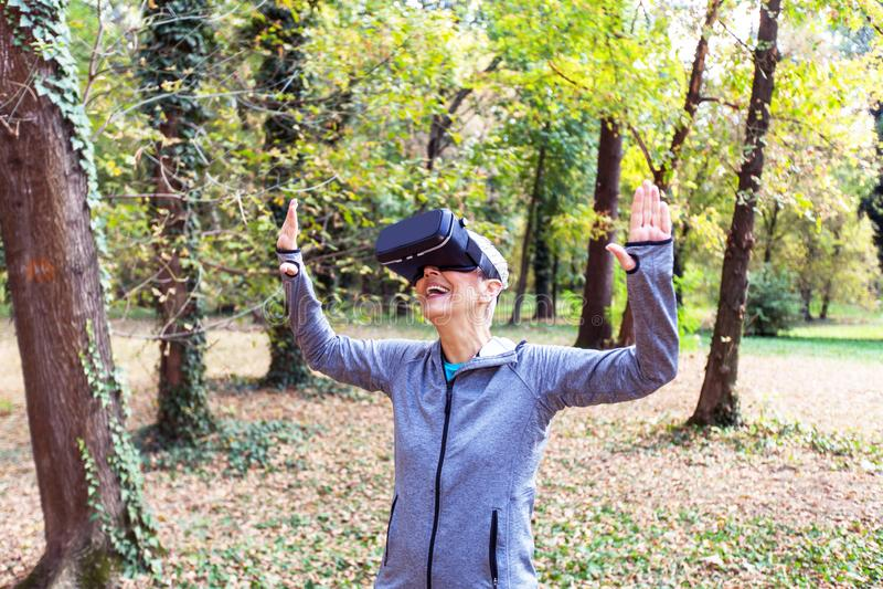 Divertimento superior da mulher com os auriculares da realidade virtual na floresta fotos de stock