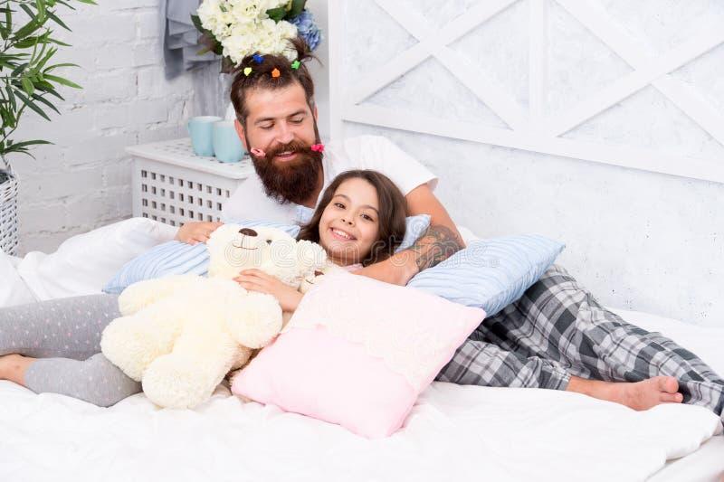 Divertiresi il partito di pigiami Pigiama party Fatherhood felice Amici intimi Papà e ragazza che si rilassano nella camera da le immagini stock