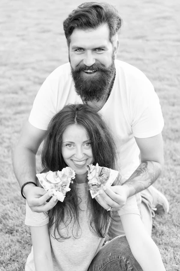 Divertiti coppia felice che mangia pizza Alimenti sani picnic estivo sull'erba verde Dieta fame fine settimana della famiglia cop fotografia stock libera da diritti