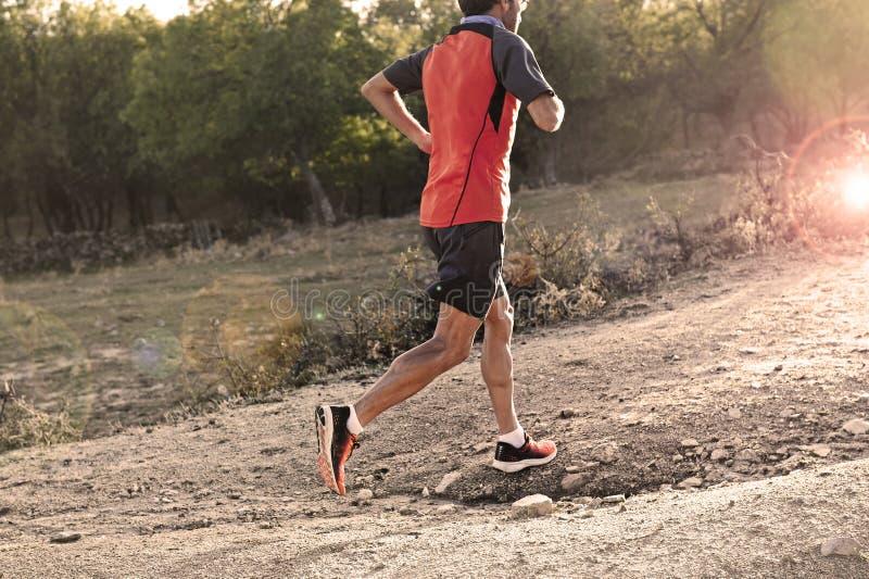 Diviértase al hombre con las piernas atléticas y musculares rasgadas que corren cuesta arriba del camino en entrenamiento del ent imagenes de archivo