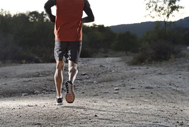 Diviértase al hombre con las piernas atléticas y musculares rasgadas que corren cuesta arriba del camino en entrenamiento del ent fotos de archivo libres de regalías