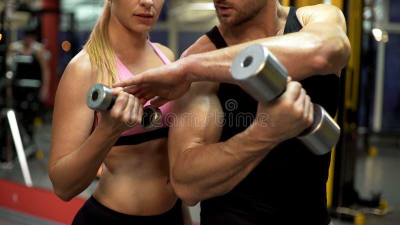 Diviértase al instructor que da instrucciones a la mujer joven cómo levantar pesa de gimnasia correctamente, servicio del gimnasi foto de archivo