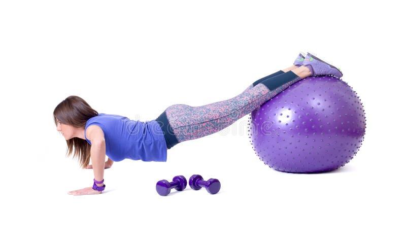 Diviértase el ejercicio de la mujer con una bola y pesas de gimnasia de los pilates foto de archivo libre de regalías