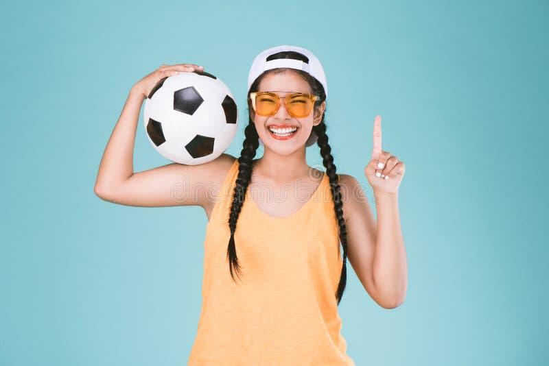 Diviértase la fan de la mujer que sostiene un balón de fútbol, celebrando el finger del punto uno encima de la muestra del ganado fotos de archivo