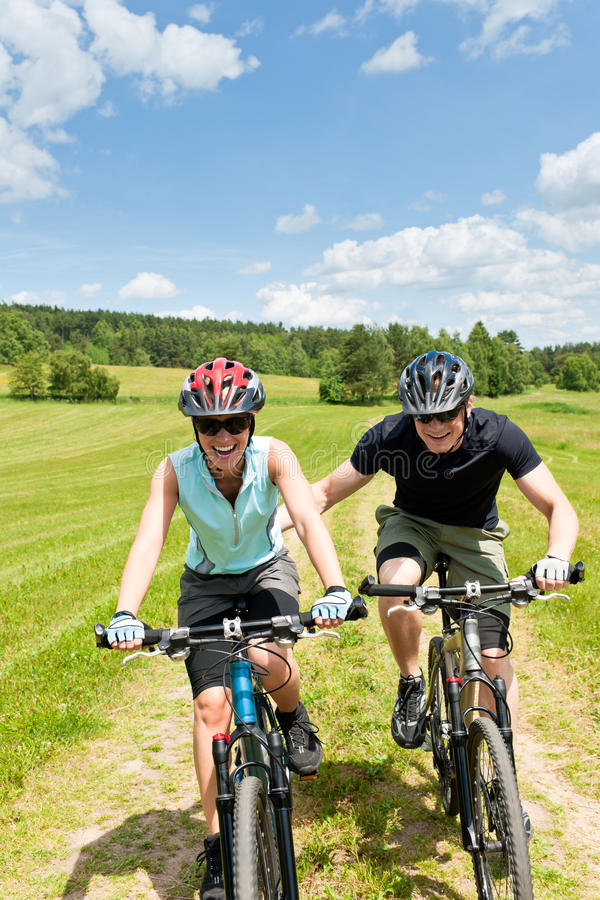 Diviértase la montaña biking - hombre que empuja a la chica joven fotografía de archivo libre de regalías