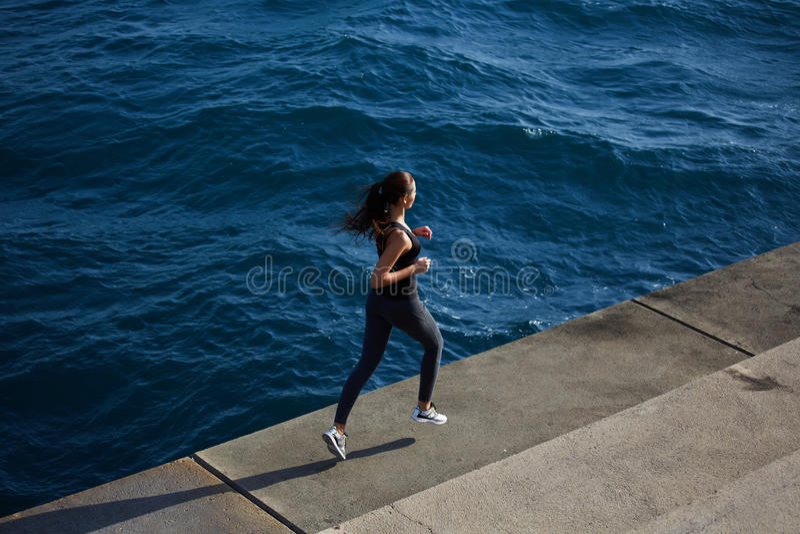 Diviértase a la muchacha en la acción que corre sobre fondo de las olas oceánicas imágenes de archivo libres de regalías