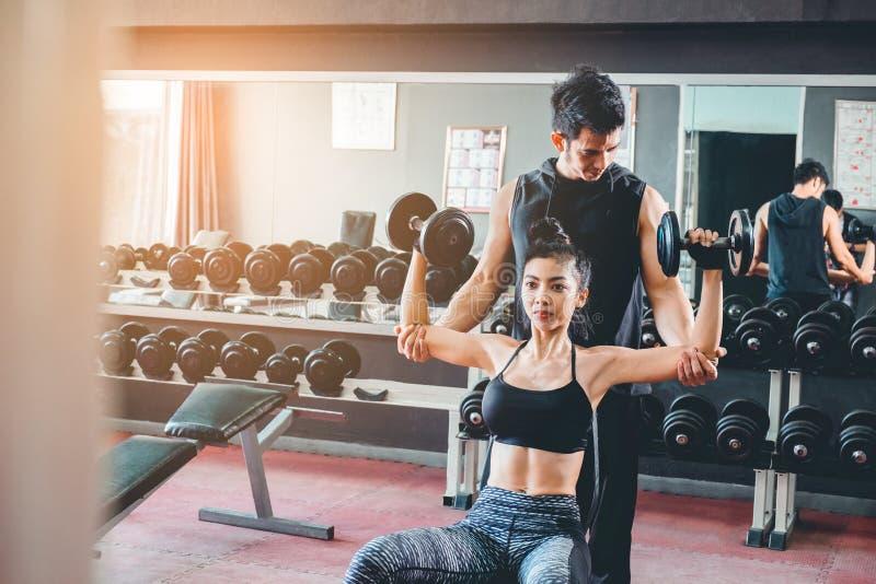 Diviértase a la muchacha que hace los ejercicios del peso que trabajan con las pesas de gimnasia pesadas h foto de archivo libre de regalías