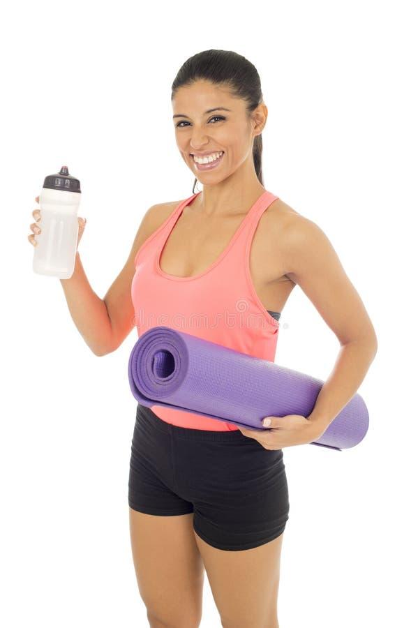 Diviértase a la mujer en la ropa de la aptitud que celebra la estera de la yoga y la botella de sonrisa del agua mineral feliz fotografía de archivo libre de regalías
