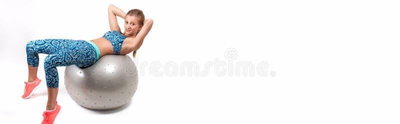 Diviértase a la mujer joven que hace ejercicios en bola de la aptitud imagen de archivo libre de regalías