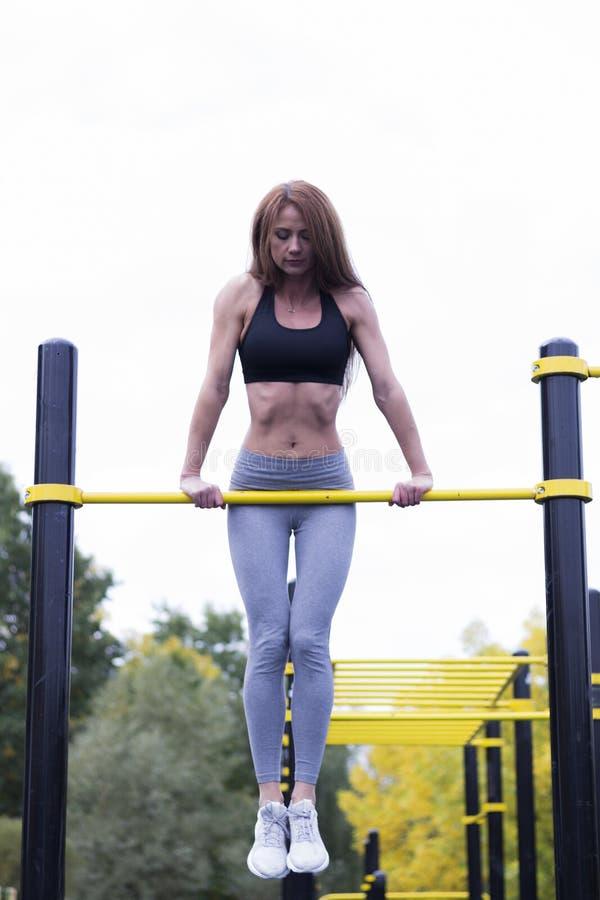 Diviértase a la mujer morena joven en ropa de deportes en la barra horizontal en gimnasio al aire libre fotografía de archivo