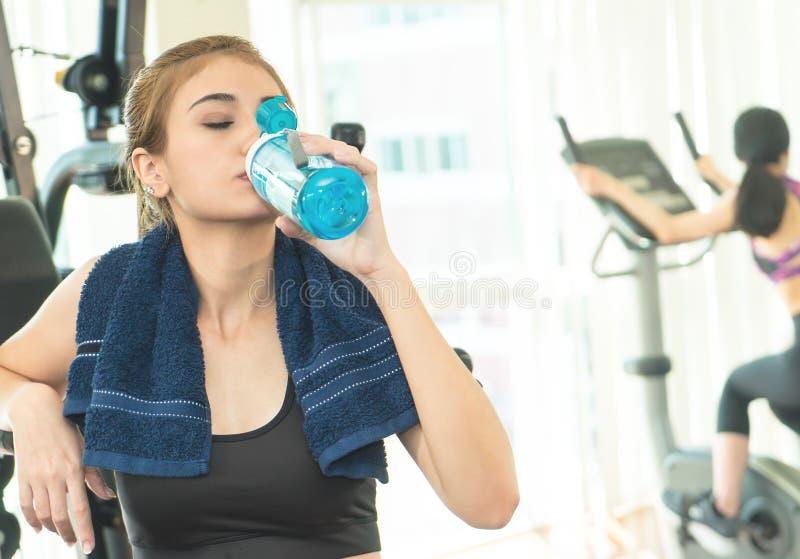 Diviértase a la mujer que bebe el agua dulce mientras que ejercita en aptitud fotos de archivo libres de regalías