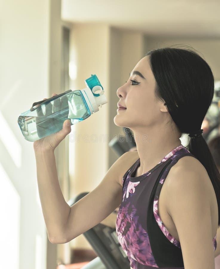 Diviértase a la mujer que bebe el agua dulce mientras que ejercita en aptitud imágenes de archivo libres de regalías