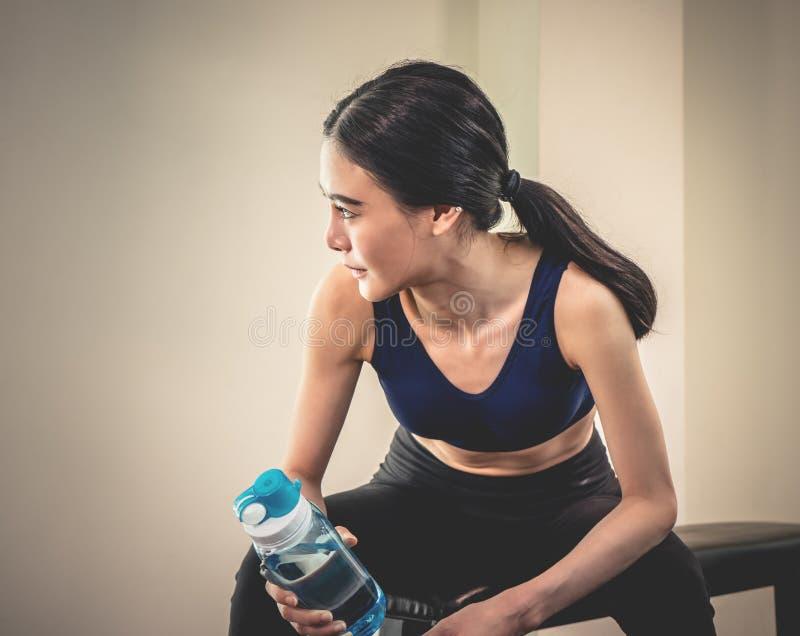 Diviértase a la mujer que bebe el agua dulce mientras que ejercita en aptitud foto de archivo