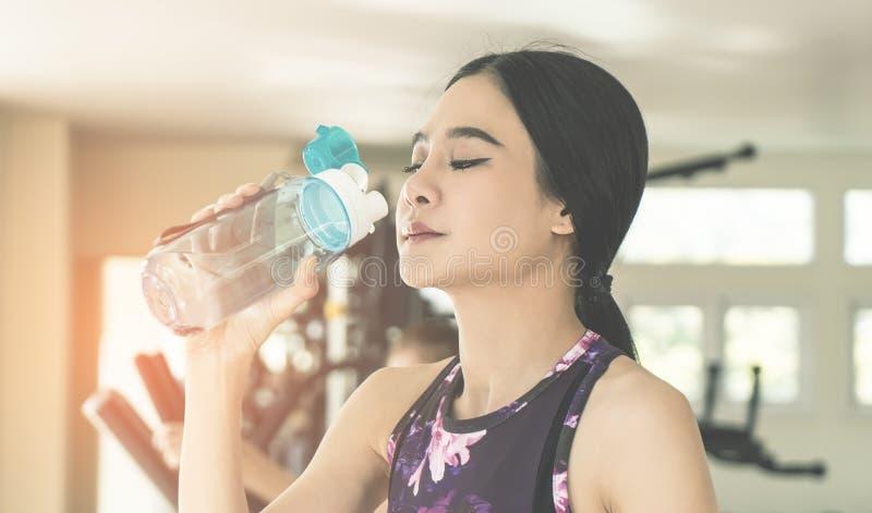 Diviértase a la mujer que bebe el agua dulce mientras que ejercita en aptitud imagen de archivo libre de regalías