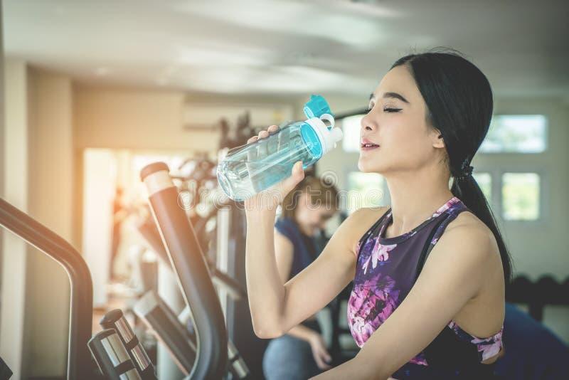 Diviértase a la mujer que bebe el agua dulce mientras que ejercita en aptitud fotografía de archivo libre de regalías