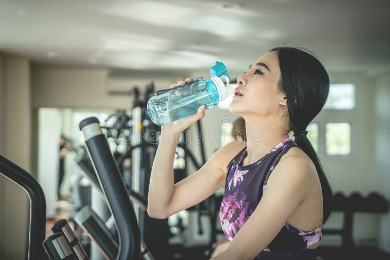 Diviértase a la mujer que bebe el agua dulce mientras que ejercita en aptitud imagen de archivo