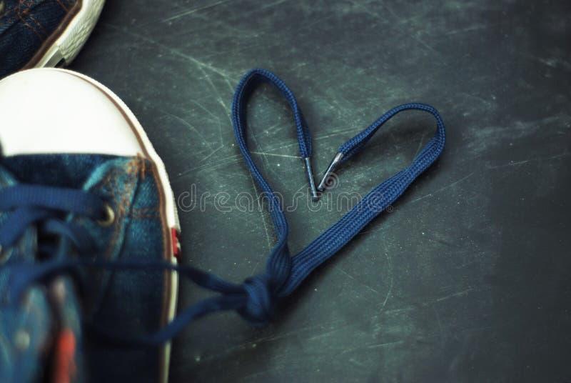 Diviértase los cordones de la forma del corazón de los niños de las botas de los tejanos sobre Grounge texturizado Chalckboard en imágenes de archivo libres de regalías