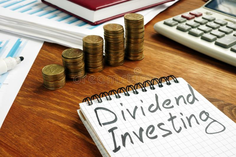 Dividend Investing sign and stacks of money. Dividend Investing sign and stacks of coins stock photo