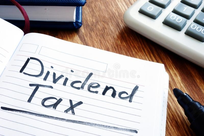Dividend tax concept. Note pad and calculator. Dividend tax concept. Note pad, calculator and pen royalty free stock image