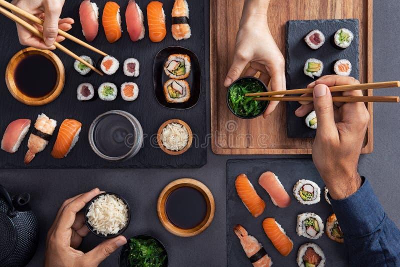Dividendo e mangiando l'alimento dei sushi fotografia stock libera da diritti