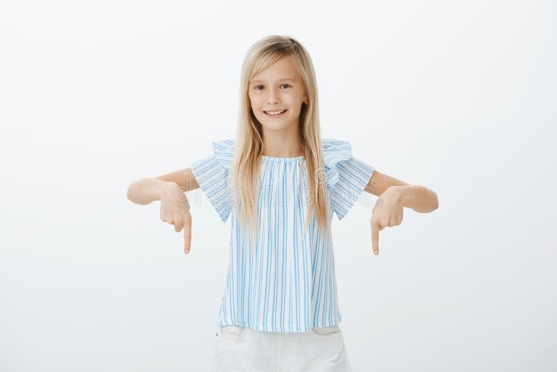 Dividendo grande segreto con i genitori Lo studio ha sparato della ragazza felice interessata con capelli giusti, indicando giù c immagine stock
