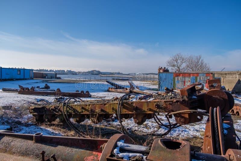 Dividido para a reconstrução a engrenagem de enrolamento do porto & o Equiptment velhos que olham sobre ao além do porto em Irvin imagem de stock royalty free