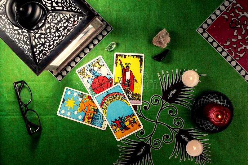 Divination by tarot cards. On a background of a green tablecloth with burning candles royalty free stock photos