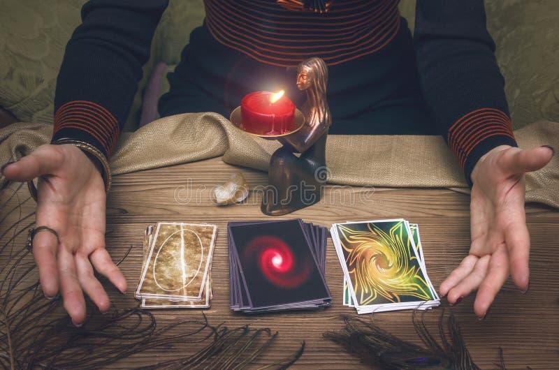 Divination. Tarot cards. Fortune teller. Woman fortune-teller chooses a deck of cards for divination stock photos