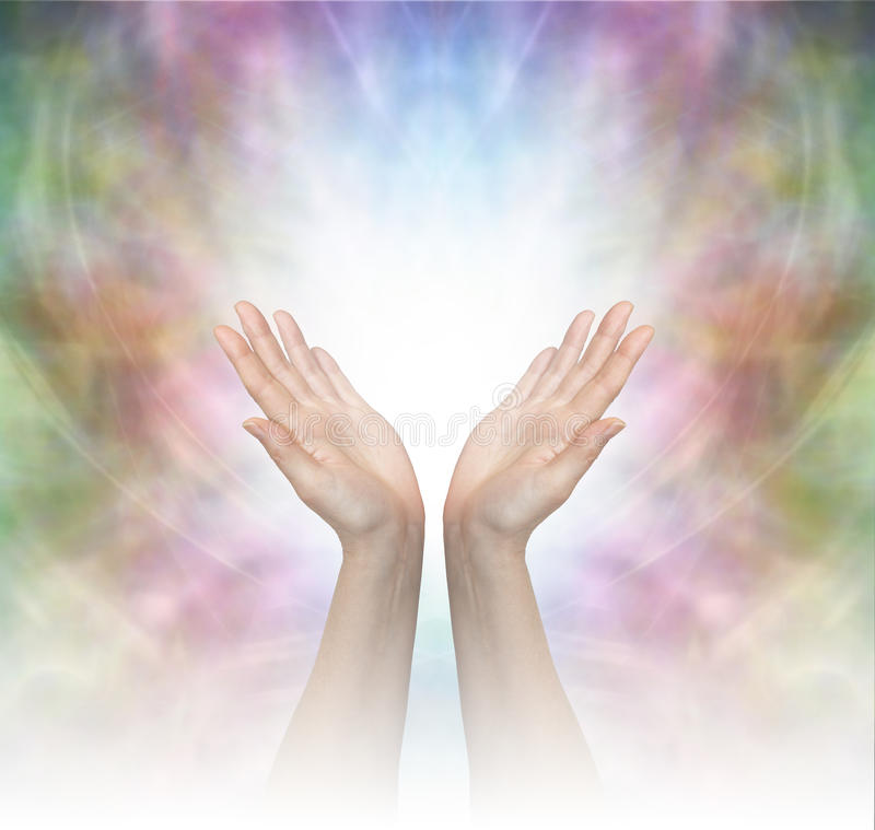 Divine Healing Energy. Female healing hands outstretched with misty white graduated light on a beautiful delicate multicolored energy field background stock images