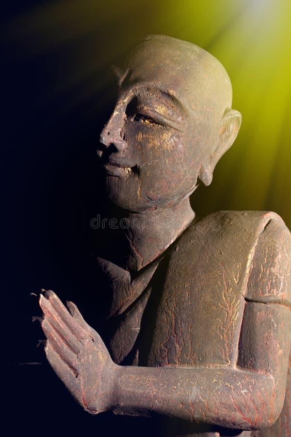 Divine light of spiritual awakening. Buddhist monk in serene prayer pose. stock image
