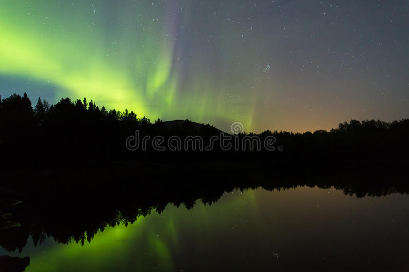 Divine scenery calm lake. Aurora borealis and stars reflects in mirror lake water with black silouette trees royalty free stock photo