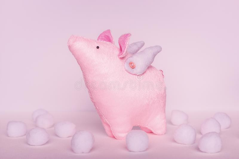 A divinely beautiful piggy angel with handmade wings stands on a white pink background with white soft balls in clouds royalty free stock photography