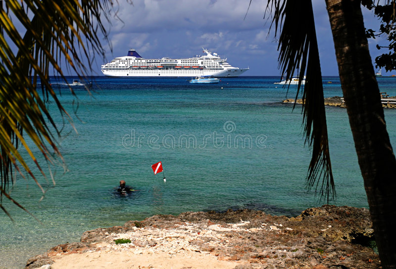 Diving around the Island. A Diver in the shallow water on an island with a cruis liner in the distance royalty free stock photos