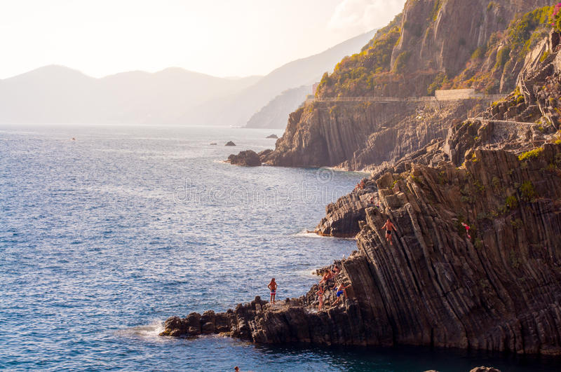 Diving from Riomaggiore cliffs. August 2 2016 Italy. Swimmers visiting the Riomaggiore cliffs during summertime for swimming and diving off the cliffs