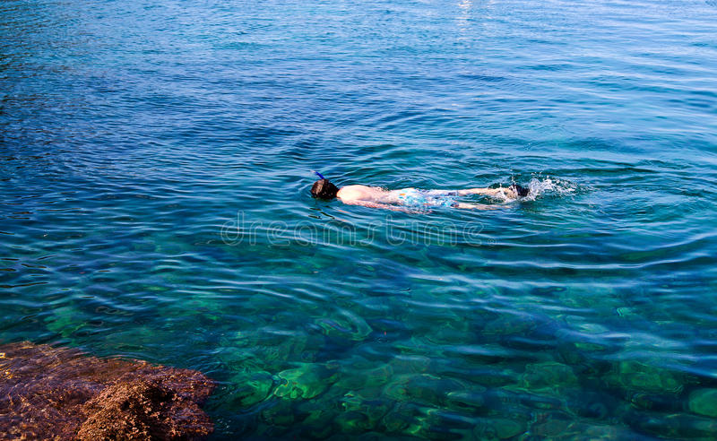 Diving, snorkelling, snorkeling, snorkel, island, indonesia, yo. A young man in a mask floats in the sea royalty free stock image