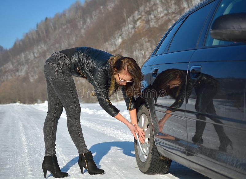 Divisão do carro do inverno - mulher nova da forma que tenta fixar o carro foto de stock