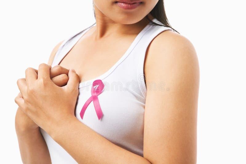 Divisa rosada en el pecho de la mujer para la causa del cáncer de pecho imagen de archivo