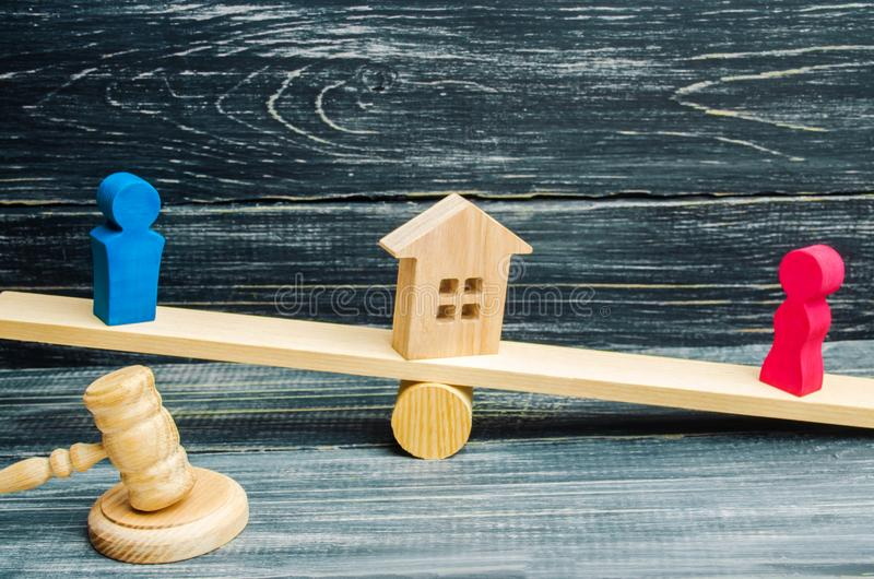 Division of property by legal means. clarification of ownership of the house. wooden figures of people. man and woman are standing royalty free stock photo