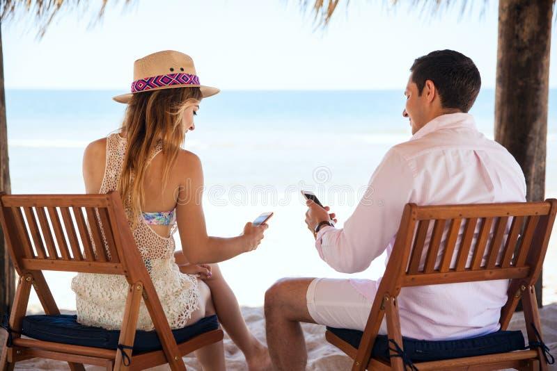 Divisione delle immagini della loro vacanza alla spiaggia fotografie stock