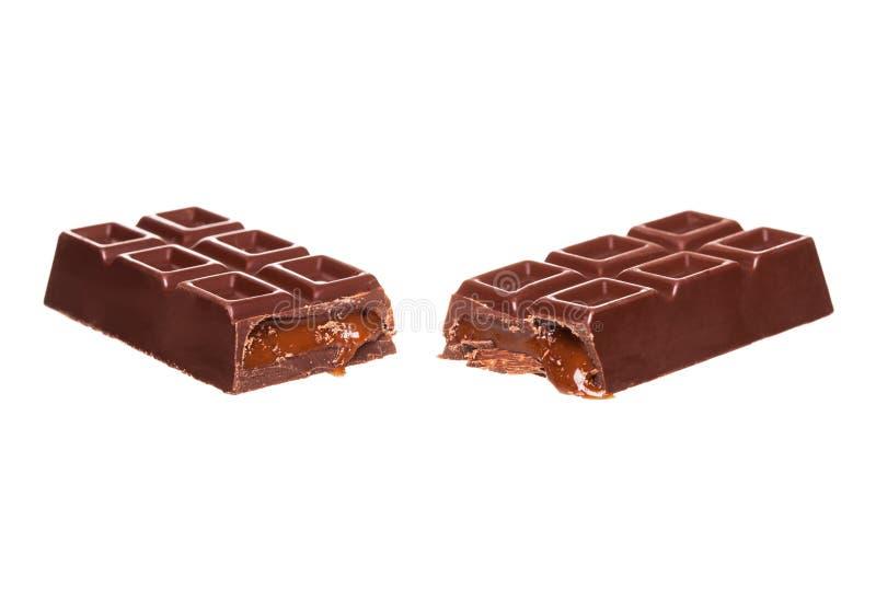 Diviso a metà la barra di cioccolato con i dadi isolati su bianco fotografie stock libere da diritti
