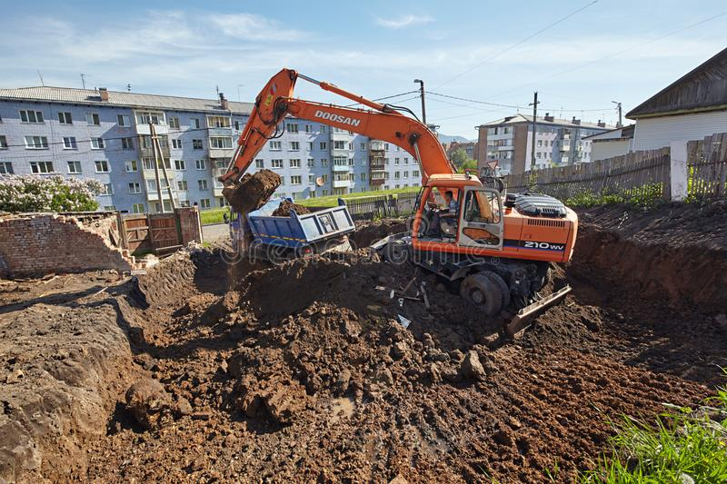Excavator woking on constraction site. Divnogorsk, Russia - June 16: Construction of a house, preparation of a trench with the technics in Divnogorsk, Russia on stock photography