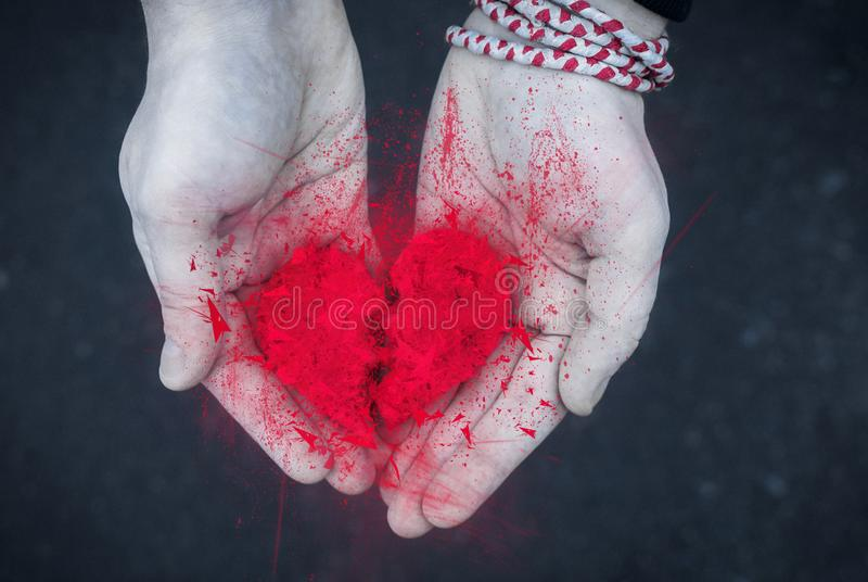Divorce concept - Explosion of Broken heart in the male hands. monochrome photo with red heart. Blak and white stock photography