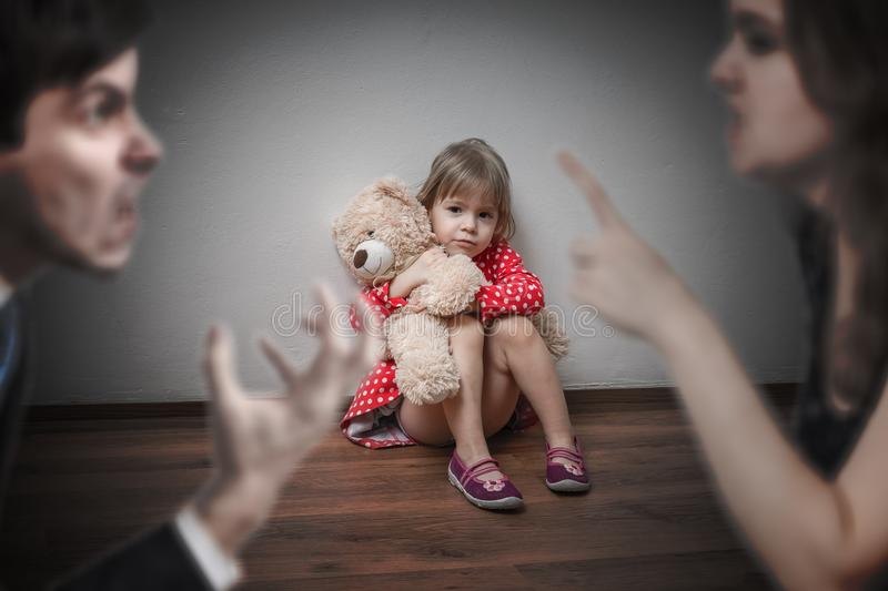 Divorce concept. Sad child is sitting at floor when parents argue. royalty free stock photography