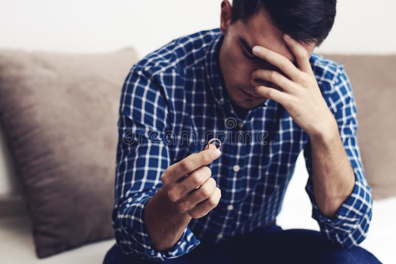 Divorce concept. Sad lonely man holding engagement ring sitting at home. Depression after a divorce. Selective focus. Heartbroken man with a wedding ring in stock image