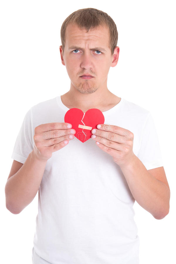 Divorce concept - sad man holding broken heart with plaster. Isolated on white background stock photography