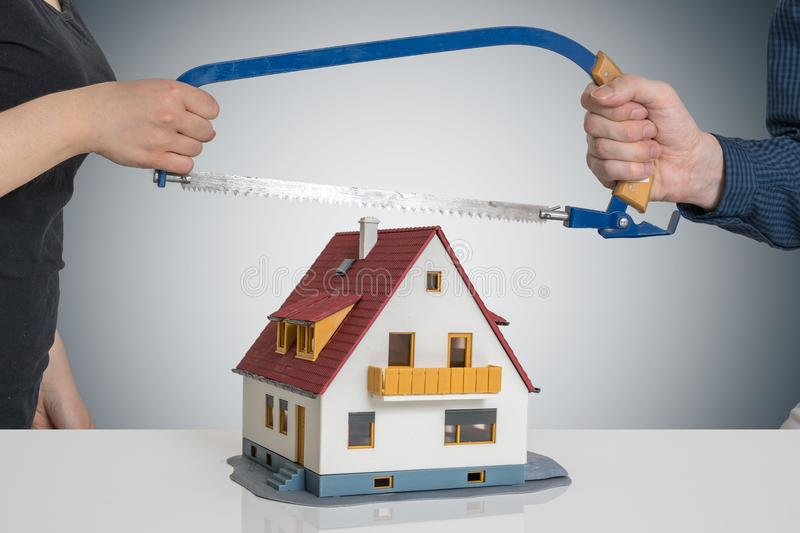 Divorce and dividing a house concept. Man and woman are splitting model of house with saw royalty free stock image